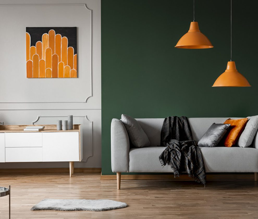 Orange lamps above grey couch in black living room interior with poster above cabinet. Real photo